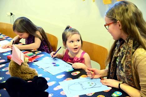 Eerica ja Jessica juttelivat ja piirtelivät Rose-Maria Laineen kanssa kevään viimeisellä satutunnilla kirjastossa.