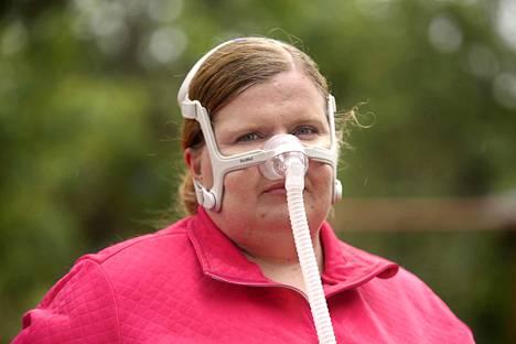Jenni Suhonen sai kesäkuun lopussa uniapnean hoitoon CPAP-laitteen, joka puskee paineella nenän kautta ilmaa sisään. Hän on ensimmäisinä päivinä totutellut maskiin pitämällä sitä yllään hyvissä ajoin ennen nukkumaanmenoa.