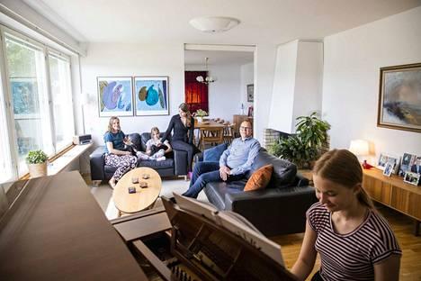 Perhe kysyi sisustussuunnittelija Hanna Rantasen mielipidettä ennen kuin osti olohuoneeseen puunvärisen 1970-luvun flyygelin. Soittaminen onnistuu kaikilta perheen tytöiltä, mutta kuvassa flyygelin ääressä istuu Anna-Liisa Ollila. Soitosta nautiskelevat sohvilla äiti Karoliina Koivuniemi-Ollila, siskot Anniina ja Annikki sekä isä Veli Ollilla.
