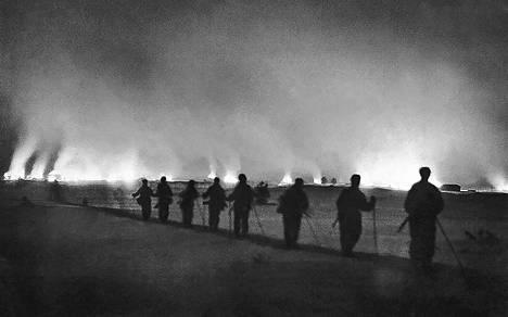 Suopassalmi palaa. Suomalaiset osasto Kalevan kaukopartiomiehet katsovat aikaansaamaansa tuhoa venäläistukikohdassa.