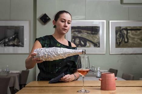 Ravintola C:n sommeliere Juulia Eloranta näyttää, miten viiniä maistetaan oikeaoppisesti. Tällä kertaa lasissa oli roseeviiniä. Ensimmäisenä tietenkin kaadetaan viini lasiin.
