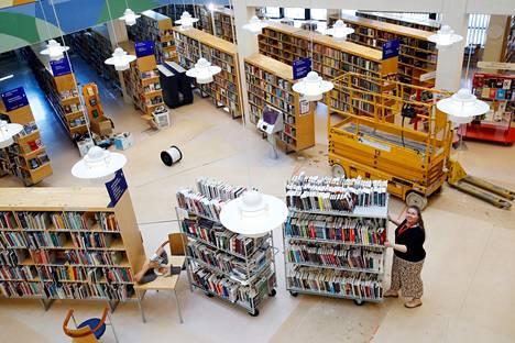 Poikkeuksellinen vuosi on vaikuttanut myös kirjastojen toimintaan. Tämä kuva on otettu toukokuussa 2020, jolloin koronaepidemian takia suljettu  Porin kirjasto avautui osittain varausten noutoa varten. Palveluvastaava  Elina Nikola järjesti varattuja kirjoja ennen kuin niitä päästiin luovuttamaan lainaajille.