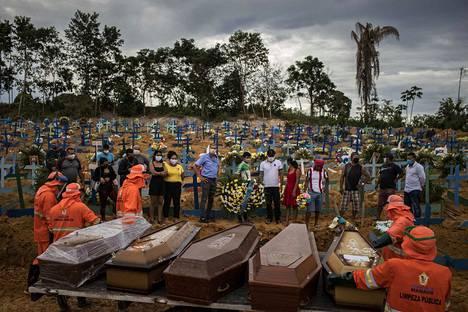 Ihmiset osallistuivat hautajaisiin joukkohaudalla Manausissa Brasiliassa 23. huhtikuuta. Joukkohautoihin on jouduttu turvautumaan koronaviruspandemian kuolonuhrien lukumäärän kasvaessa.