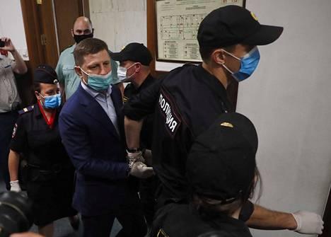 """Poliisit vievät kuvernööri Sergei Furgalia oikeussaliin Moskovassa. Venäjän tapaan syytetty on käsiraudoissa ja kuuntelee käsittelyä eristetystä """"apinahäkistä""""."""