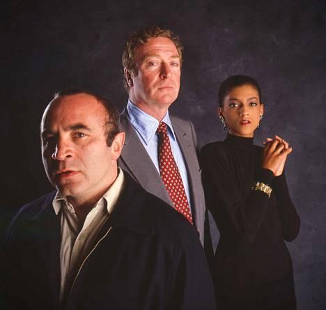 Lontoon alamaailmaan sijoittuva Mona Lisa kertoo entisestä vangista (Bob Hoskins), joka kiintyy tummaan puhelintyttöön (Cicely Tyson) kuskatessaan häntä asiakkaalta toiselle. Gangsteripomo Mortwellina (keskellä) on Michael Caine.