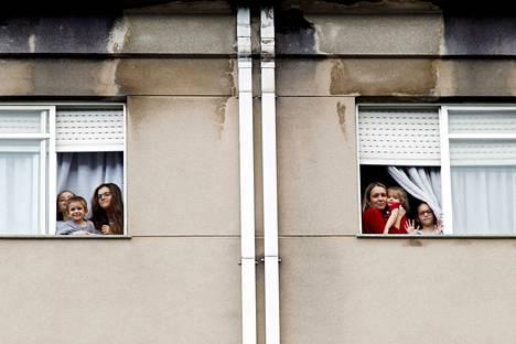 Suositukset välttää sosiaalisia kontakteja ja erilaiset rajoitukset ovat lisänneet perheiden ja pariskuntien yhteistä aikaa ympäri maailman. Perheet kurkkaavat kerrostalon ikkunoista Ferrolissa Espanjassa.