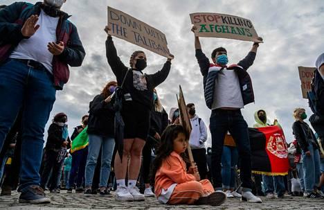 Mielenosoittajat näyttävät kylttejä parlamenttirakennuksen edessä Berliinissä 17. elokuuta 2021 vaatiakseen turvallista kulkua Afganistanin kansalaisille.