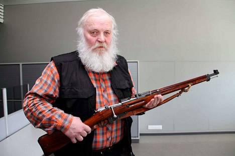 """Historian ja metsästyksen harrastaja Rauno Kaappa esittelee metsästyskäytössä olevaa sotilaskivääriä, mikä tunnettiin kutsumanimellä """"pystykorva"""". Pystykorva oli yleinen jalkaväen ase viime sodissa."""