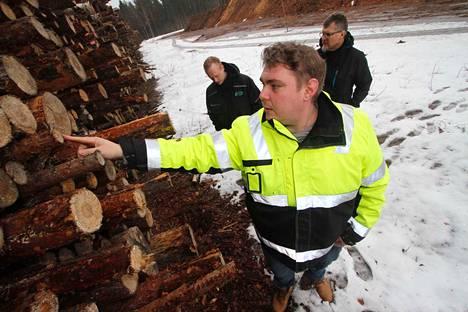 Kuljetusesimies Markku Kiviluoma, edessä, tarkastelee energiapuun laatua. Taustalla hankintaesimiehet Tuomas Leponiemi ja Tapio Heikintalo.