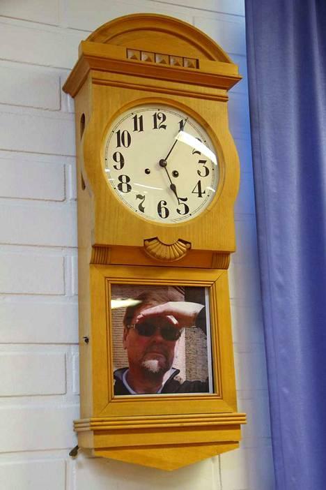 Rehtori Juhani Grönroos tarkkailee kellosta.