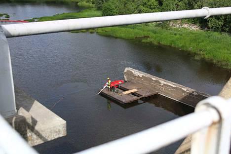 Sukeltajat tekevät betonirakenteen korjauksia veden alla.