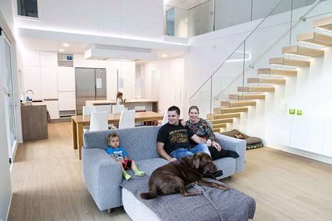Kahden kerroksen korkuinen olohuone on Anna Chronsin ja Petri Haatajan unelmakodin sydän. Myös lapset Onni, 3, Isla, 6 (taustalla) ja koira Ansa nauttivat hiljattain valmistuneesta kodista Vesilahdessa.