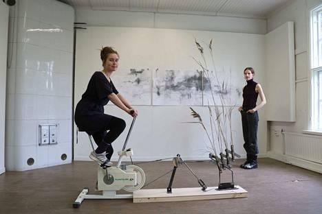Iina Vartia polkee Tuulikone 2.0 -teostaan. Taustalla Annika Takkala ja hänen kolmiosainen piirrossarjansa Pitkä toivo.