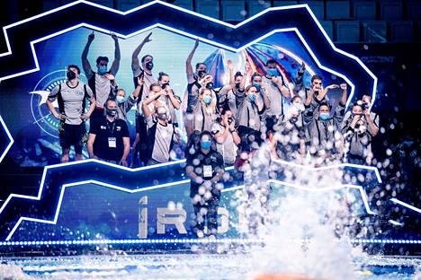 Uimarit seuraavat kilpailuja joukkueaitioissaan maskit kasvoillaan. Team Ironin Ida Hulkko ja Jenna Laukkanen kuvan keskellä.