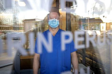 Suojattuna. Vahtimestari Jani Haapaniemi poimii koronavastaanotolle tulevan potilaan sisään lukitun ulko-oven takaa. Ensimmäisenä potilaalle laitetaan kasvomaski, jonka saa poistaa vasta palattuaan ulkoilmaan.