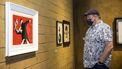 Mänttäläinen Tony Hietala tutkii Love is in the Air -teosta. Banksy maalasi alkuperäisen teoksen muuriin Israelin ja Palestiinan rajoille. Useampi näyttelyvieras huomautti teoksen olevan maiden välisen konfliktin kiihtyessä jälleen poikkeuksellisen ajankohtainen.