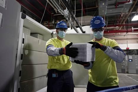 Työntekijät pitelivät koronavirusrokotetta sisältävää laatikkoa, joka oli lähdössä matkaan Pfizer Kalamazoon lääketehtaalta Michiganin Portagesta sunnuntaina.