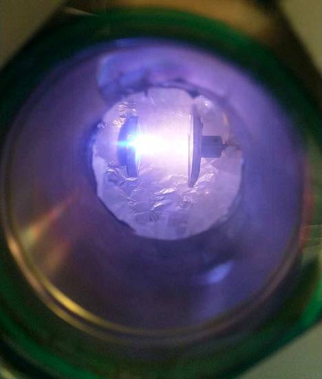 Kun kiteistä alumiinioksidia pommitetaan tutkimuslaitteen sisällä laserpulsseilla (vasemmanpuoleinen alusta), kiteet hajoavat atomeiksi ja ne muuntuvat plasmaksi. Tuhansiin asteisiin kuumentunut plasma jäähtyy sekunnin miljardiosissa huoneenlämpöiseksi, ja oikeanpuoleiselle alustalle kerääntyy plastista lasia. Alustojen välinen etäisyys on noin viisi senttimetriä.