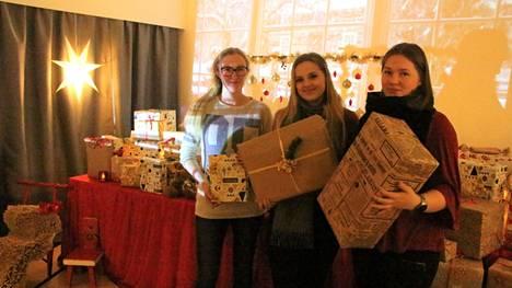 Sisustusalan opiskelijat Riikka Vuorinen, Julia Eklund ja Sara Luoto ovat rakentaneet jouluisen tonttupajan lahjapaketteineen.