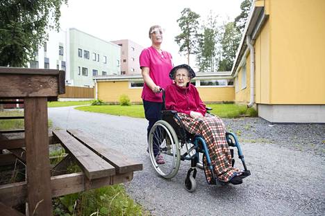 Palvelukoti Honkalan asukas Toini Westergård ulkoilee päällikkö Anne Peltomäen avustamana. Peltomäki toivoo, ettei vierailuja tarvitsisi kieltää enää kokonaan.