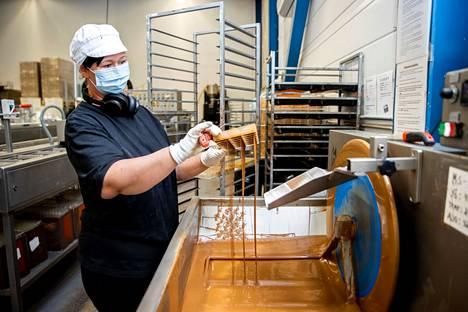 Marjo Herckmann valaa konvehteihin suklaiset kannet. Työssä ei saa hidastella tai kiirehtiä, jotta kansista tulee juuri sopivan paksuisia.