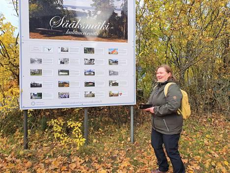 Hankepäällikkö Petra Pikkanen toivoo uuden elämystaulun tuovan lisää kävijöitä Sääksmäen kulttuuriraitille. Taulu seisoo Sääksmäen kirkon tapulia vastapäätä pysäköintipaikan laidalla.