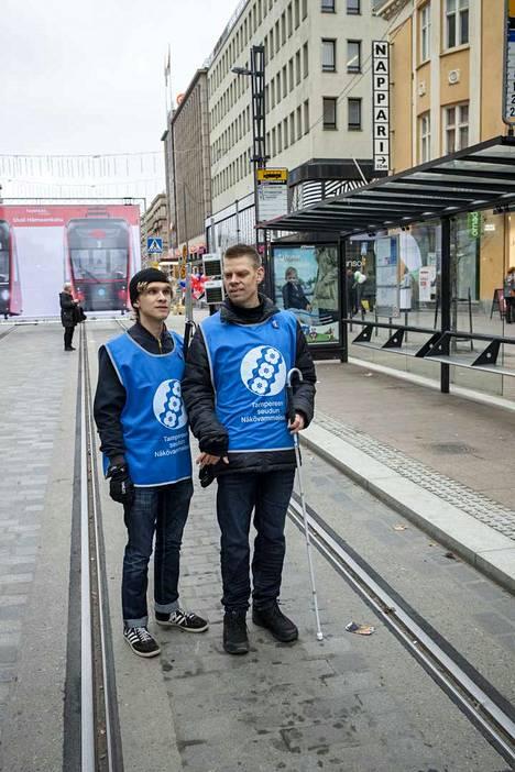 –Tavoitteemme ei ole varsinaisesti jakaa näkövammaisuuden ilosanomaa, vaan tutkia, millainen uusi Hämeenkatu täältä päästä on ja vastata kaupunkilaisten kysymyksiin, sanoi Tampereen seudun näkövammaisten Tuukka Ojala seuranaan Eero Hauskamaa. Roskis oli heillä etsinnässä, muttei tahtonut löytyä, kun se oli uudella Hämeenkadulla eri paikassa. –Haasteena ovat Hämeenkadun risteävien katujen ylityspaikat, joita ei kepillä havaitse, he sanoivat. Vaihtoehtona on tällöin ihmisvirtojen seuraaminen.