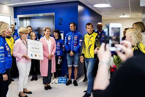 Aamulehden Jukolan viestin julkkis- ja lukijajoukkueiden keräämä lahjoitus luovutettiin uudelle lastensairaalalle maanantaina. Palkintoa oli luovuttamassa Kooveen Raimo Arvola (keltainen takki, farkut) ja sen vastaanotti ylilääkäri Marja-Leena Lähdeaho (vaaleanpunainen neule). Kuvassa myös projektipäällikkö Susanna Lohiniemi (vaaleanpunainen neuletakki).