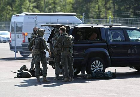 Poliisin erikoisjoukot seisoivat ruotsalaisen Hallbyn vankilan edustalle parkkeeratun auton vieressä keskiviikkona 21. heinäkuuta. Vankilassa keskiviikkona vartijat panttivangeiksi ottaneita vankeja epäillään kidnappauksesta Ruotsissa.