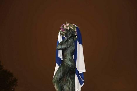 Helsinkiläinen Elmo Laine asetteli siniristilipun Havis Amandan päälle.
