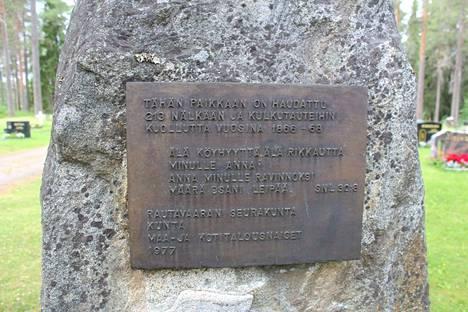 """Jykevän kiven seinämään kiinnitettyyn laattaan on kirjoitettu, että """"Tähän paikkaan on haudattu 213 nälkään ja kulkutauteihin kuollutta vuosina 1866-68""""."""