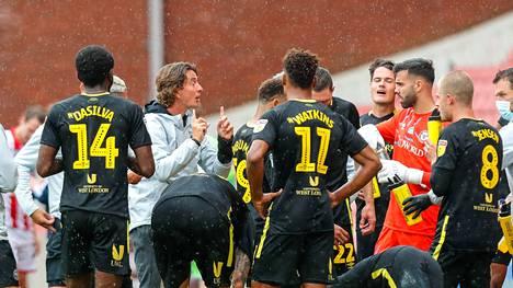 Brentfordin valmentaja Thomas Frank ohjaa mustapaitaista joukkuettaan Stoke-kamppailun sateessa.