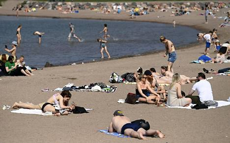 Auringonottajia Hietaniemen uimarannalla helatorstaina 13. toukokuuta.