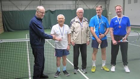 Keuruun Tennisseuran kunniapuheenjohtaja Paavo Hautanen jakoi SM-mitalit ja onnittelee senioreita saavutuksista. Pelaajat mitalit kaulassa vasemmalta M85-sarjan Väinö Taipale (90 v.) ja Antti Airaksinen (89 v.) sekä M60-sarjan Timo Levonen ja Rauno Harjunmäki.