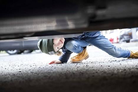 Perheen kuopus Niilo Taipalmaa tutkii Subaru Forest e-Boxerin maavaraa, joka muuten on 22 senttimetriä. Virallinen jalkapallo mahtuisi juuri pyörimään sen alta.
