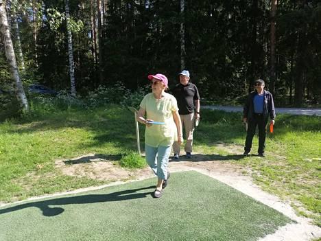 Katriina Pekkarinen, Pauli Nokelainen ja Pentti Pekkarinen aloittelevat kierrosta Ketvelniemen frisbeegolfradalla. Alkuun otetaan pienet verryttelyheitot.