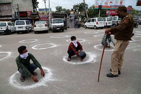 Jammun and Kashmirin poliisit pakottivat karanteenimääräystä rikkovia ihmisiä seisomaan maahan piirrettyjen ympyröiden sisällä.