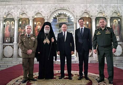 Venäjän presidentti Vladimir Putin ja Syyrian Bashar al-Assad tapasivat Damaskuksessa tiistaina. Syyrian presidentin oikealla puolella poseerasi Venäjän puolustusministeri Sergei Shoigu ja Putinin vierellä kreikkalais-ortodoksinen patriarkka.