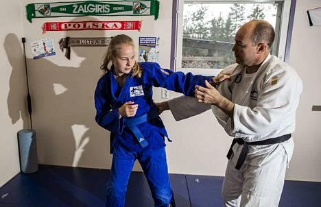 Judoka Pihla Salonen harjoittelee kotinsa autotallin yhteydessä olevassa treenitilassa. Harjoitusvastustajana isä Sami.