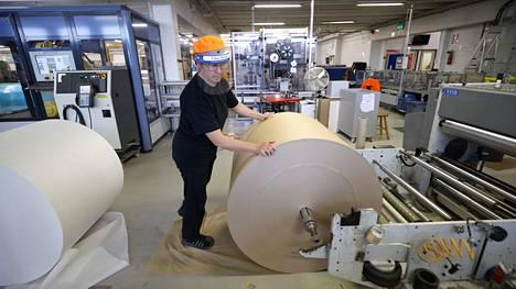 Tanja Lehtonen on tehnyt näitä hommia 17 vuotta. Kolmivuorotyössä viihtyvä nainen käyttää toista kolmessa vuorossa käyvistä leivinpaperikoneista ja vaihtaa taas kerran rullaa.