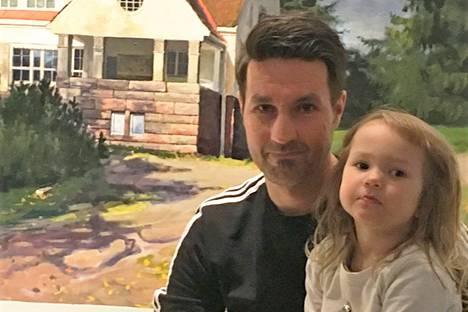 Friida-tyttö on tässä päässyt isän syliin. Taustalla on Janne Kukkosen maalaama tilaustyö. Myös lapset pääsevät välillä maalausten aiheiksi.