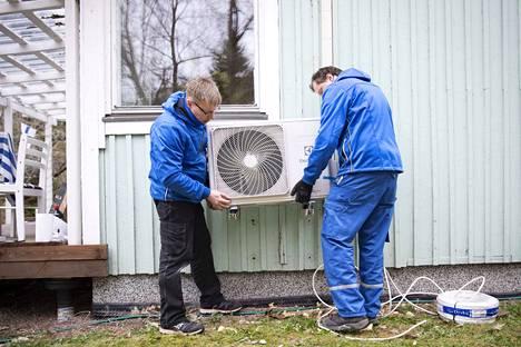 Jarno Huttunen (oikealla) ja Marko Aalto Kylmäkarhut Oy:stä asentavat uutta ilmalämpöpumppua vanhan tilalle Vanha-Ulvilassa. Laitteiden kysyntä on korkealla ja asennuksissa on pitkästi jonoa.