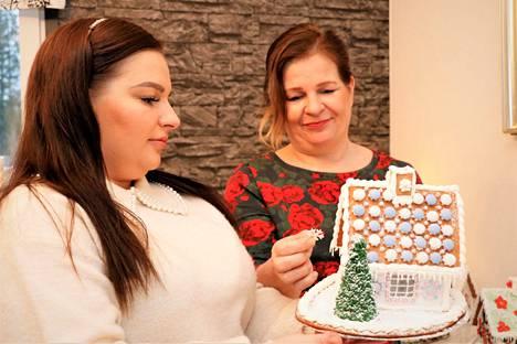 Sari Hjelt ja Kirsi Kankkonen ovat tehneet täksi jouluksi enemmän piparkakkutaloja kuin koskaan. Talojen lisäksi he rakentavat piparkakkutaikinasta karkilla täytettäviä rekiä.