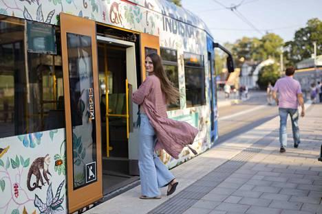 Laura Kunnas astumassa itse suunnittelemansa kuosin vuoraamaan ratikkaan Tukholmassa.