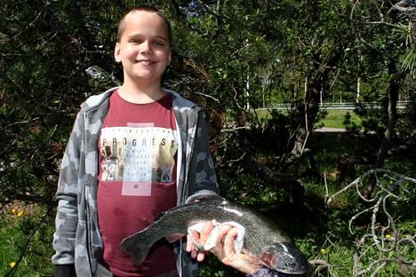 Daniel Sundberg on tyytyväinen kalamies. Koululaisen mato-onkeen tarttui reilun kilon painoinen kirjolohi.