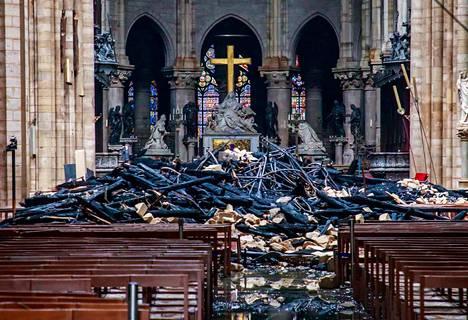 Tältä näytti tiistaina Notre Damen katedraalin sisätiloissa tuhoisan palon jälkeen. Kuvassa näkyy katedraalin romahtaneen katon hiiltyneitä jäännöksiä ja muuta romua.