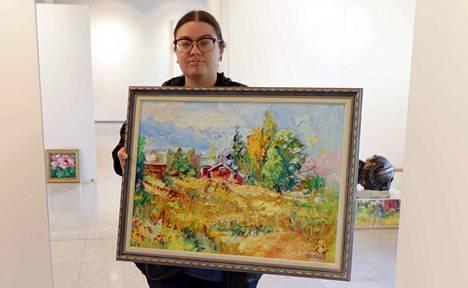 Taiteilija Julia Pinezhaninovalla on käsissä maisema Savonlinnasta.