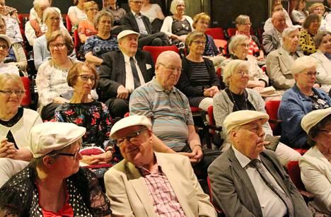 Valkoisia lippalakkeja yleisön joukossa. Korpirastas-juhlaan oli kutsuttu kaikki 17 Runon ruusu -tunnustuksen saanutta henkilöä. Einari-lippalakit on suunnitellut ja valmistanut Fredrikson, ja ne ovat uniikkituotantoa.