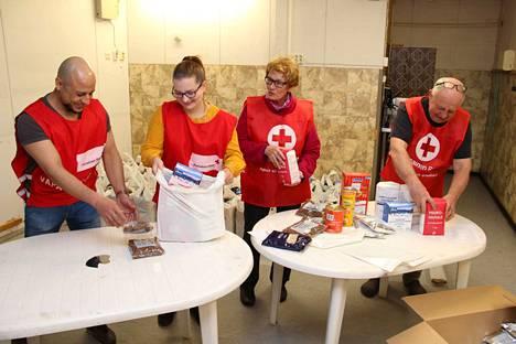 Vapaaehtoiset Ajed Ajad ja Julia Vornanen olivat tulleet auttamaan Kaisa ja Ilmo Saarta ruokakassien pakkaamisessa.