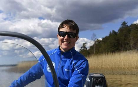 Valmennuspäällikkö Ilona Hiltunen seuraa soutajien otteita moottoriveneestä käsin.